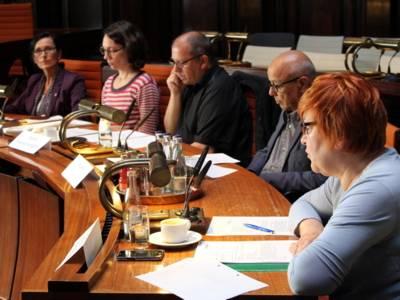Fünf Personen - drei Frauen und zwei Männer - sitzen im Hodlersaal hinter Pulten. Die Frau rechts blickt auf ein Papier vor sich und spricht.
