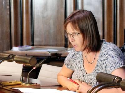 Eine Frau sitzt im Hodlersaal an einem Pult und spricht.