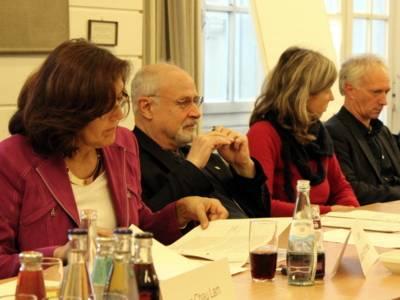 Vier Personen - drei Männer und eine Frau - sitzen im Gobelinsaal nebeneinander hinter Tischen, auf denen Getränke und Gläser stehen. Eine blättert in Papieren, die vor ihr auf dem Tisch liegen.