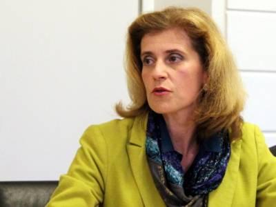 Eine Frau sitzt im Gobelinsaal und spricht.