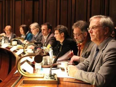 Sieben Personen - zwei Frauen und fünf Männer - sitzen im Hodlersaal nebeneinander hinter Pulten