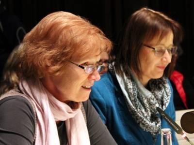 Zweil Frauen sitzen im Hodlersaal. Die links sitzende spricht und blickt nach vorne. Die andere schaut auf Unterlagen, die auf dem Pult vor ihr liegen .