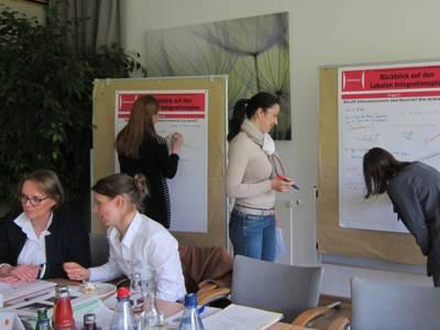 Drei Frauen stehen an zwei Plakatständern, auf denen sie Notizen eintragen. Davor sitzen zwei weitere Frauen an Tischen, von denen eine zur anderen spricht.