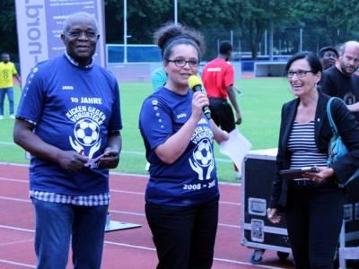Drei Personen - zwei Frauen und eine Mann - stehen nebeneiunander im Stadion. Die Frau in der Mitte hält ein Mikrofon in der Hand.