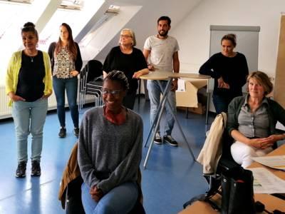 Sieben Personen - sechs Frauen und ein Mann - sitzen und stehen in einem Raum und blicken nach vorn.