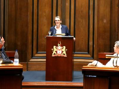 Eine Frau steht im Hodlersaal des Neuen Rathauses an einem Stehpult und spricht in ein Mikrofon.