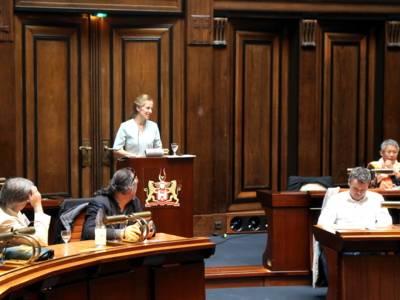 Eine Frau steht im Hodlersaal des Neuen Rathauses an einem Stehpult und spricht. Links und rechts vor ihr sitzen Teilnehmer*innen und blicken zu ihr.