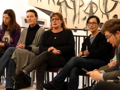 Fünf Personen - vier Frauen und ein Mann - sitzen im Foyer des Hauses der Jugend auf Stühlen. Eine der Frauen spricht.