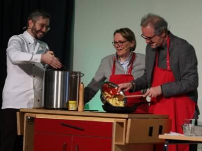 Drei Personen - zwei Männer und eine Frau - tragen rote Schürzen und stehen hinter einer mobilen Kochstelle.