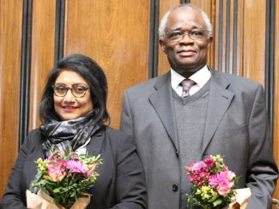 Zwei Personen - ein Mann und eine Frau - stehen vor der Doppeltür im Hodlersaal des Neuen Rathauses und blicken in die Kamera. Dabei halten sie jeweils einen Blumenstrauß in der Hand.