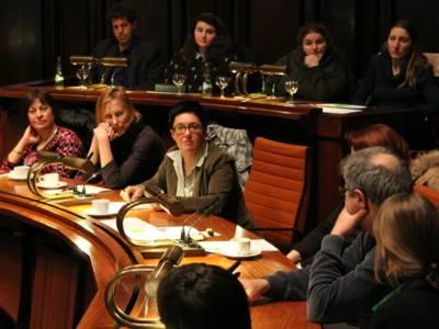 Elf Personen sitzen im Hodlersaal hinter Pulten. Eine davon spricht. Die anderen blicken zu ihr.