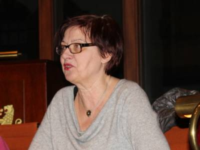 Eine Frau sitzt im Hodlersaal hinter einem Pult und spricht