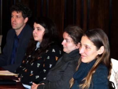 Vier Personen - drei Frauen und ein Mann - sitzen im Hodlersaal hinter Pulten und blicken nach vorne