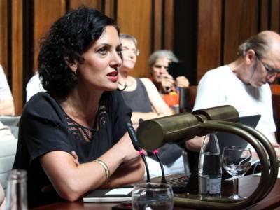 Eine Frau sitzt im Hodlersaal hinter einem Pult, auf dem ein aufgeklapptes Notebook steht, und spricht.