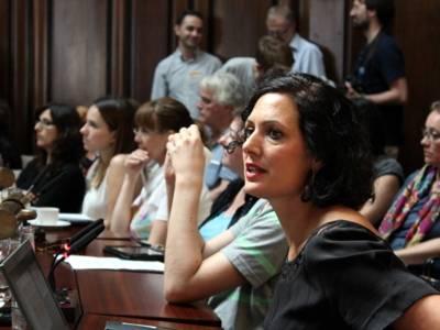 Eine Frau sitzt im Hodlersaal hinter einem Pult und spricht.