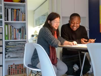 Eine Frau und ein junger Mann sitzen in einem Wohnzimmer an einem Tisch und blicken auf Papiere, die vor ihnen liegen.