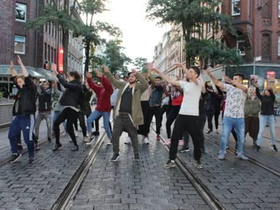 Etwa 25 Jugendliche stehen versetzt in drei Reihen, drehen sich nach rechts und heben dabei die Arme mit ausgestreckten Handflächen in die selbe Richtung.