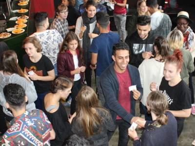 Etwa 15 Jugendliche stehen in einem Raum in kleinen Grüppchen. SIe unterhalten sich paarweise und schütteln sich die Hände.