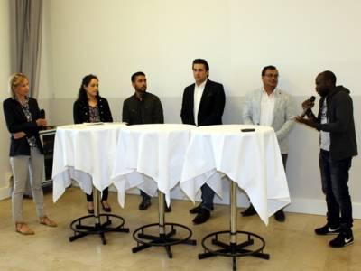 Sechs Personen stehen nebeneinander hinter zwei runter Stehtischen. Der Mann auf der rechten Seite hält ein Mikrofon in der Hand und spricht.