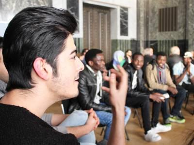 Ein Mann sitzt im Hodlersaal und spricht, während er mit seiner rechten Hand gestikuliert. Hinter ihm sind etwa zwölf weitere Personen erkennbar, die in seinem, oder dem benachbarten Stuhlkreis sitzen.