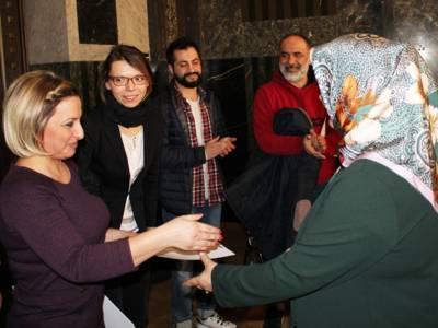 Fünf Personen stehen im Mosaiksaal des Neues Rathauses. Eine Frau überreicht einer anderen eine Urkunde und streckt ihr zur Gratulation ihre rechte Hand entgegen.