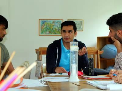 EIn Jugendlicher sitzt am Kopfende eines Tisches und spricht. Links und rechts von ihm sitzen zwei weitere Jugendliche und blicken zu ihm.