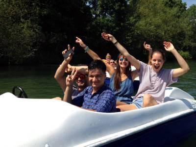 Vier Jugendliche sitzen in einem Tretboot und winken in die Kamera. Dahinter sind zwei Personen auf einem weiteren Tretboot zu erkennen.
