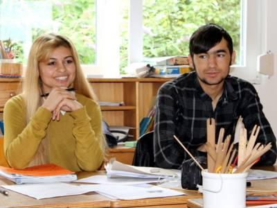 Zwei Jugendliche - eine Frau und ein Mann - sitzen nebeneinander hinter Tischen.