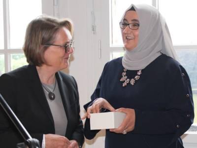 Zwei Frauen stehen im Mosaiksaal des Neuen Rathauses. Eine davon hält ein helles Kästchen in der Hand.
