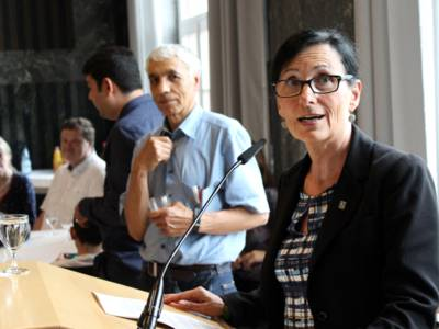 Eine Frau steht im Mosaiksaal des Neuen Rathauses hinter einem Redern*innenpult und spricht.
