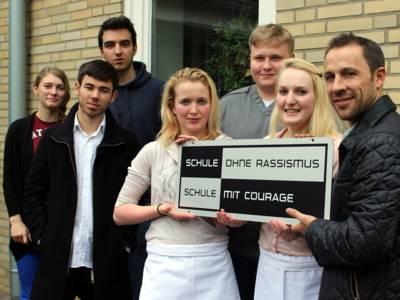 Ein Mann steht mit sechs Jugendlichen - drei Jungen und drei Mädchen - vor der Schule und hält mit ihnen zusammen das SOR-SMC-Schild hoch.