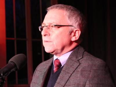 Nahaufnahme eines Mannes mit Brille, der in ein Mikrofon spicht.