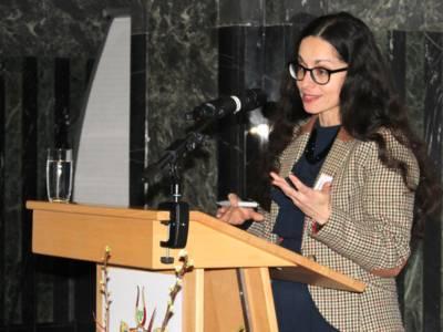Eine Frau steht im Mosaiksaal des Neuen Rathauses hinter einem Stehpult und spricht.