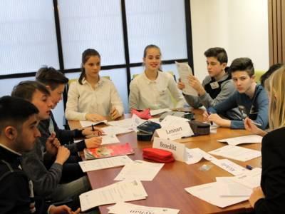 Etwa zehn Jugendliche sitzen hinter zusammengeschobenen Tischen.