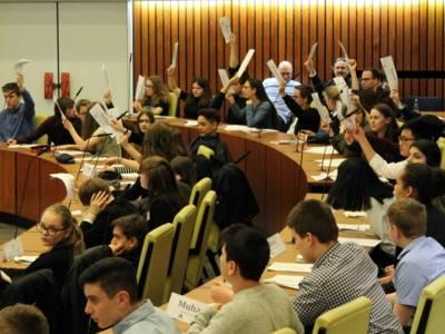 Etwa 50 Schüler/innen sitzen im Ratssaal des Neuen Rathauses und halten ihre Namensschilder zur Abstimmung hoch.