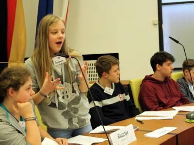 Eine Schülerin steht im Ratssaal hinter einem Pult und spricht. Dabei gestikuliert sie.