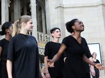 Vier Jugendliche - drei Mädchen und ein Junge - stehen dunkel gekleidet in der Kuppelhalle des Neuen Rathauses.