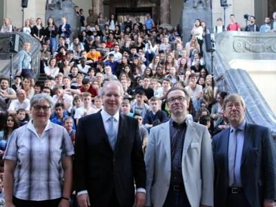 Vier Personen stehen in der Kullelhjalle des Neuen Rathauses vor der großen Treppe, auf der sich die eingeladenen Jugendlichen befinden.