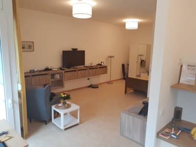 Zimmer mit Sessel, Rollcontainer und an der Wand festgeschraubten Sideboards, auf denen zahlreiche elektronische Geräte zur alltäglichen Unterstützung liegen.