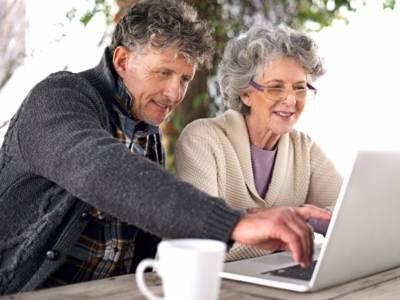 Eine ältere Dame mit Brille und ein Mann sitzen vor einem Laptop