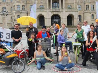 Gruppenfoto: Jongleurinnen, Clowns, Radfahrer und weitere Personen, die beim Autofreien Sonntag als Aussteller oder Gastronomen vertreten sind, haben sich vor dem Hannoverschen Rathaus versammelt.