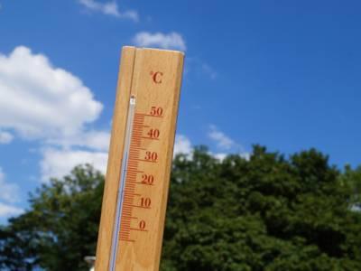 Ein Thermometer vor Sommerhimmel zeigt 32 Grad Celsius