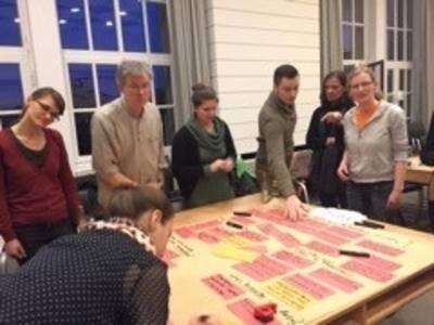 Teilnehmerinnen und Teilnehmer des Plenums stehen um einen Tisch und sammeln auf einem Plakat ihre Ideen zum Thema Plastik.