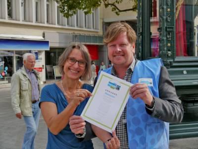 Susanne Wildermann vom Agenda21- und Nachhaltigkeitsbüro und Carsten Elkmann von TransFair e.V.  präsentieren am Kröpke die Fair Trade Town Urkunde für Hannover
