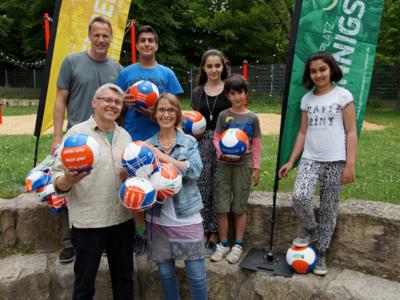 Drei Erwachsene und vier Kinder halten fair gehandelte Fuß- und Volleybälle in den Händen und lächeln.
