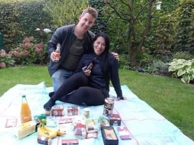 Eine Frau und ein Mann sitzen auf einer Picknickdecke, vor ihnen Lebensmittel aus dem fairen Handel.
