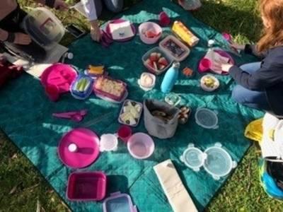 Schüler*innen sitzen um eine Picknickdecke, auf der verschiedene Snacks in Mehrwegdosen stehen.