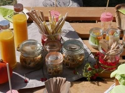Auf einem Tisch stehen die Zutaten für ein Picknick in Gläsern und Flaschen bereit.