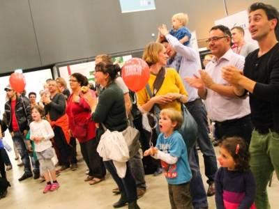 Blick ins Publikum: Man sieht Kinder und Erwachsene, die zur Musik auf der Bühne klatschen.