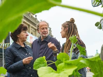 Eine junge Frau spricht mit einem älteren Paar über ökologische Landwirtschaft